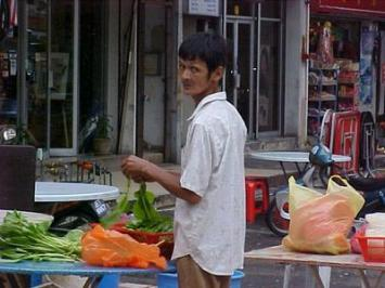 A rather candid shot of a street-stall cook prepping his veggies for the evening.