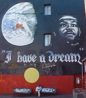 In the heart of it all there is this mural of our planet earth and Rev. Dr. Martin Luther King, Jr., superimposed over the Aboriginal flag. The Black represents the Aboriginal people, the Red is symbolic of the earth and its spiritual ties, & the Yellow is the sun-the giver of life. It was painted by Andrew Aiken and Juilee Pryor.